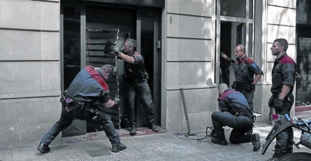 Unos mossosd'esquadraderriban la puerta del club cannábico Hardala en la calle de Bailén de Barcelona esta semana. (1)